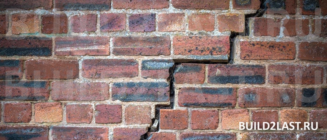 Трещина в кирпичной стене в результате подъёма почвы от морозного пучения