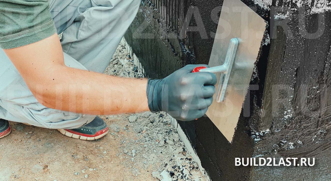 Гидроизолирование стены фундамента битумной мастикой. Важно работать в перчатках потому, что битум трудно отмывается с рук.