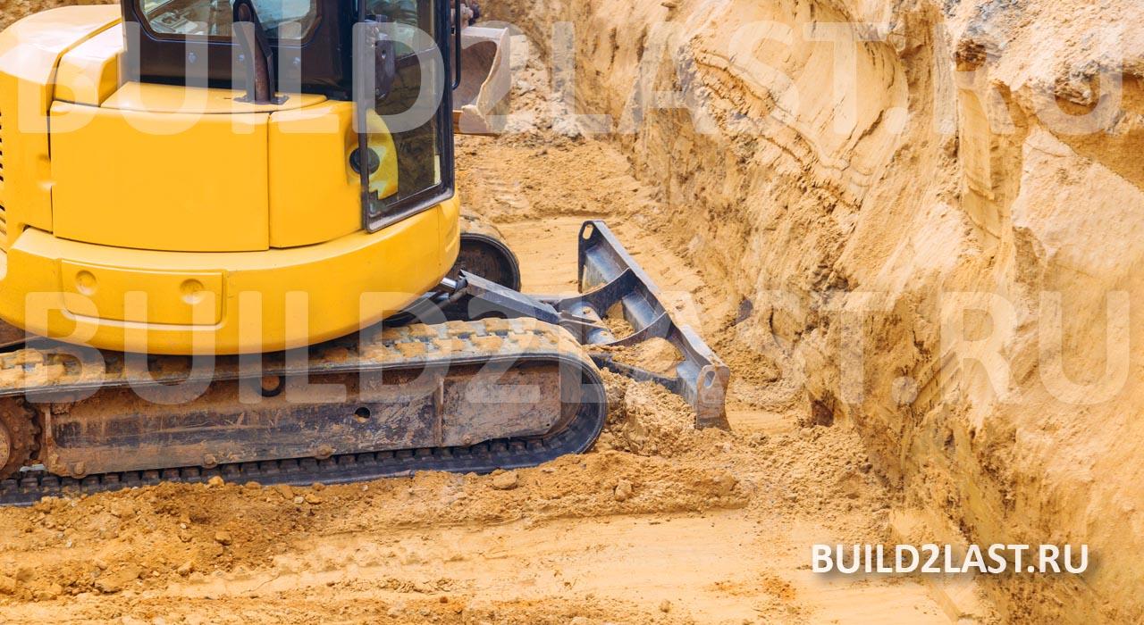 Бульдозер ровняет дно котлована перед засыпкой щебня при замене грунта