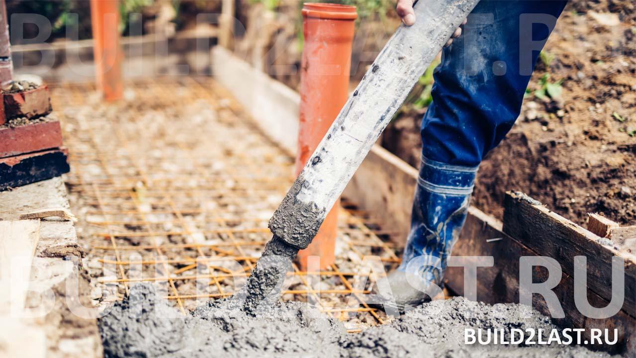 Заливка отмостки бетоном, на фото видно армирование отмостки и приёмные трубы ливневой канализации